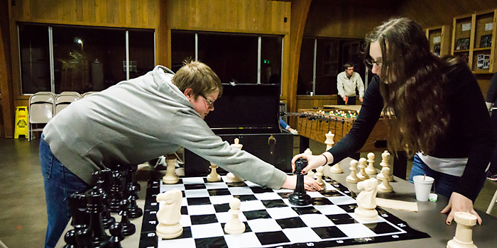 A couple of Winter Retreat Campers play a game of giant chess at Camp Yamhill