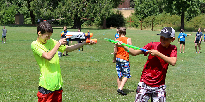 7th and 8th grade children having a water fight during summer camp at Camp Yamhill