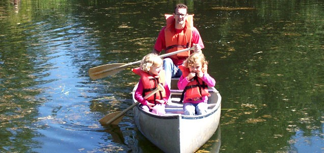 A dad and his two daughters canoeing on the Camp Yamhill pond