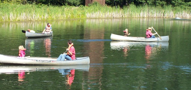 Several dads with their kids canoeing on the Camp Yamhill pond