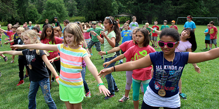 Campers at 3rd and 4th grade camp get warmed up in the morning with songs and dancing