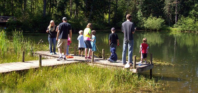 Several dads and their children fishing off the dock of the Camp Yamhill pond
