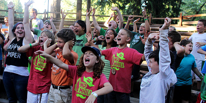Enthusiastic campers sing around Camp Yamhill's campfire